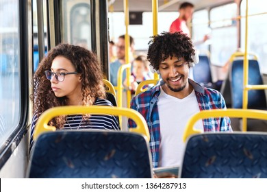 Two young persons sitting next to each other in city bus. Girl looking through window while guy having earphones on ears and using tablet.