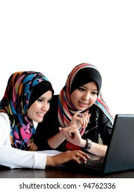Two young pretty Asian muslim business woman in head scarf with  laptop against white background