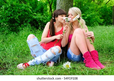 two young pretty girls with flowers sitting on a grass