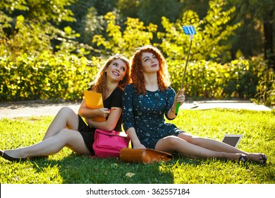 Two young pretty girls make selfie. Students are sitting on the lawn in the park. Self-portrait. Shooting on the phone. Selfie stick. BFF