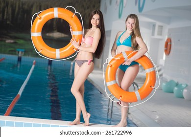 Two young pretty girls standing in swimming pool and holding a lifebuoy