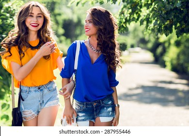 Two young pretty girls walking in sunny summer park.  Girlfriends enjoying their time together and celebrate  holidays.