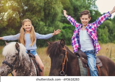 Two young pretty kids riding a horses on a yellow field