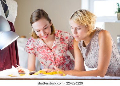 Two young pretty needlewomen in studio working at order