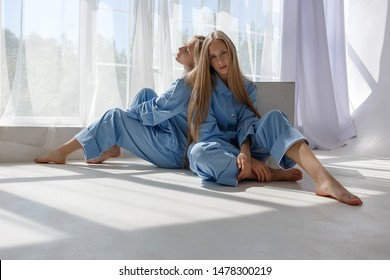 two young pretty twin girls in identical blue suits with long blond hair sitting on white cyclorama floor in studio in pattern of light and shadow near window, leaning on wooden cube with bare legs