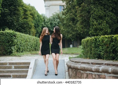 two young pretty woman in a little black dress indoor