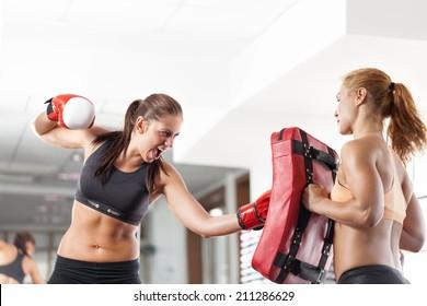 Two young pretty women boxing