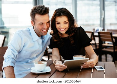 Two young professionals browsing internet during a coffee break