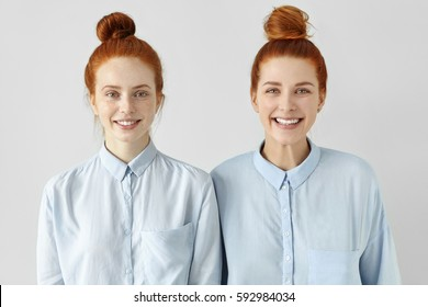 Two young redhead Caucasian females looking alike wearing same formal light-blue shirts, looking at camera, smiling happily, standing close to each other against white studio wall background