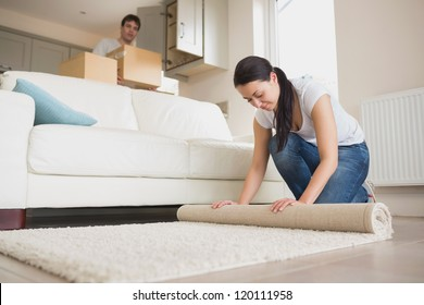 Two young relocating people moving into their house and furnishing the lounge