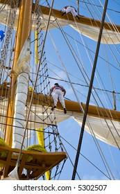 two young sailor climb on a school ship