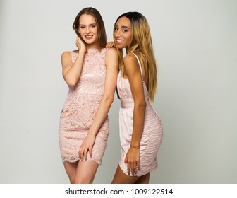 Two young sexy women in pink dress, isolated on gray background