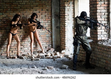 Two young sexy women with rifles and soldier