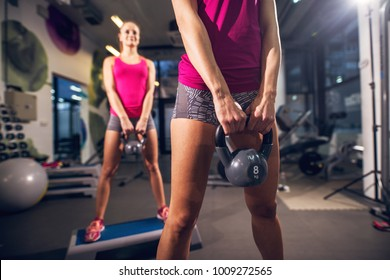 Two young shape athletic attractive slim fitness active girls doing exercises with kettlebells while holding in front and standing on the steppers in the modern gym.