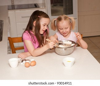 Two young sisters baking cupcakes in their kitchen at home in their domestic kitchen.