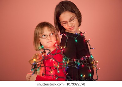 Two young sisters with christmas lights wrapped up around them acting silly