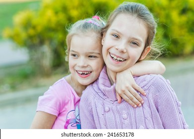 Two young sisters hugging, in summer city park.