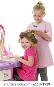 Two young sisters playing beauty parlor. On a white background. Focus on beautician.