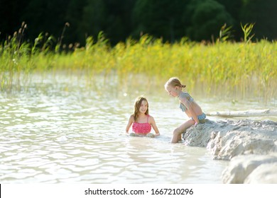 Two young sisters taking healing mud baths on lake Gela near Vilnius, Lithuania. Children having fun with mud. Kids playing with medicinal clay.