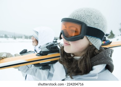 Two young skiers carrying ski on shoulder, looking away, close-up