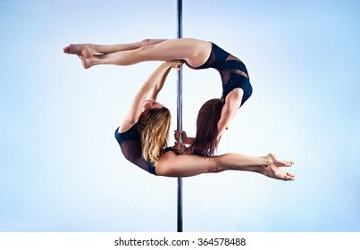 Two young slim pole dance women on white and blue wall background