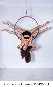 Two young slim sports women hanging on ring upside down in bright white interior