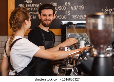 Two young smiling barista at work. Professional barista team brewing coffee using coffee machine. Happy young man and woman developing own coffee business. Coffee shop concept.