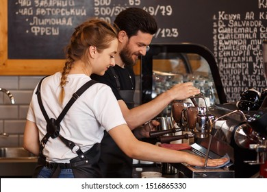 Two young smiling barista at work. Professional barista team brewing coffee using coffee machine in coffee shop. Happy young man and woman developing own coffee business.