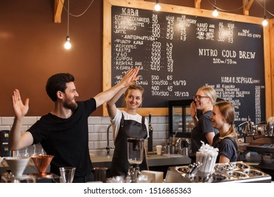 Two young smiling barista at work. Professional barista team brewing coffee using  machine in coffee shop. Happy young man and woman developing own coffee business. Coffee shop concept.