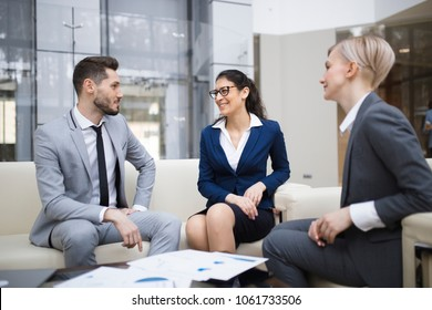 two young smiling Caucasian women and one man at a business meeting in the business center