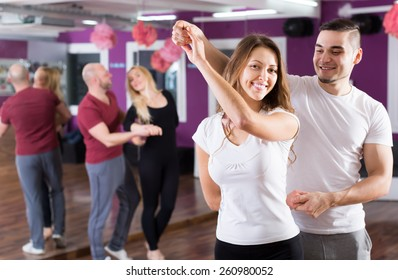 Two young smiling couples having dancing class in club