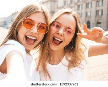 Two young smiling hipster blond women in summer white t-shirt clothes. Girls taking selfie self portrait photos on smartphone.Models posing on street background.Female showing positive face emotions