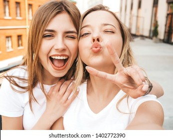 Two young smiling hipster blond women in summer clothes. Girls taking selfie self portrait photos on smartphone.Models posing on street.Female making duck face and shows peace sign