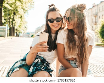 Two young smiling hipster women in summer clothes. Girls taking selfie self portrait photos on smartphone.Models sitting in the street.Female going crazy and making funny faces in sunglasses