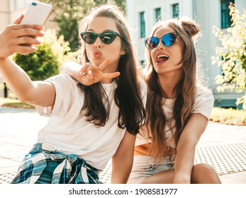 Two young smiling hipster women in summer clothes. Taking selfie self portrait photos on smartphone.Models sitting in the street.Female going crazy and making funny faces in sunglasses