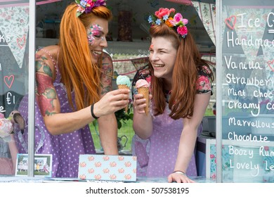 Two young smiling ladies with red hair wearing vintage dresses holding ice cream in truck