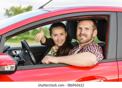 Two young smiling people in a red car. Girl showing thumbs up. Concept of travel, rent or buying car.