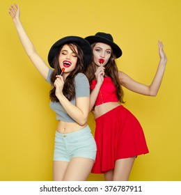 Two young smiling pretty beautiful girls wearing hats holding candies. Studio portrait of two cheerful sexy women over yellow background.