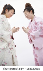 Two young smiling woman in Japanese kimonos bowing to each other
