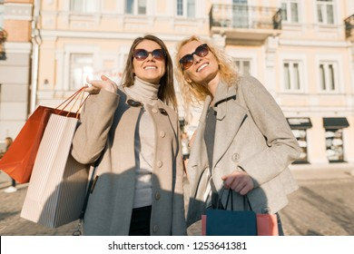 Two young smiling women on a city street with shopping bags, sunny autumn day, golden hour.