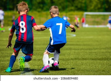 Two young soccer players kicking soccer ball on grass pitch. Youth sports competition between two school sports teams. Kids football tournament game.