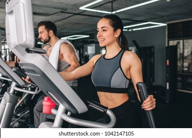 Two young sport folks are exercising on the elliptical machine. They are having a tough workout.