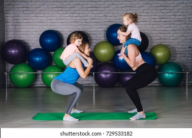 Two young sports mom and baby girls do exercises together in the gym. Parent and child healthy development, fitness and relaxation. Healthy lifestyle concept photo. Toning.