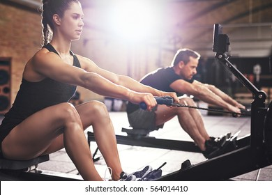 Two young sportsmen having hard workout on rowing machines in gym.
