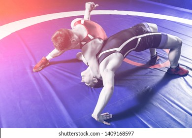 Two young sportsmens wrestlers in red and blue uniform wrestling against wrestling carpet, view above.