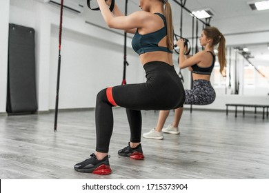Two young sporty girls training in fitness club with modern TRX equipment and performing squats with suspension straps and elastic band  during effective full body workout.