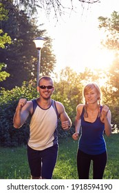 Two young sporty man and woman exercising in park at summertime season.