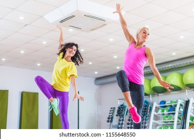 Two young sporty women exercising in fitness studio, dancing, doing cardio, working on balance and coordination.
