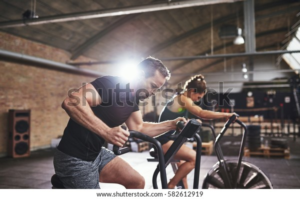 Two young strong sportsmen having hard workout on cycling machines in light gym.