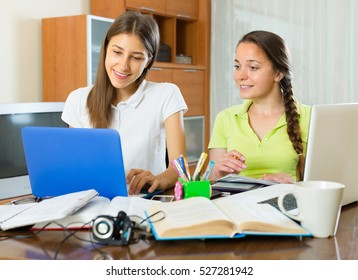 Two young student girls with laptops studying together at the table